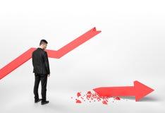 Achtermening van een zakenman die gebroken pijl bekijken die daling van de grafiek Stock Afbeeldingen
