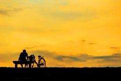 Achtermening van een zitting van het paarsilhouet op Stoel bij kleurrijke su Stock Fotografie
