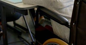 Achtermening van gehandicapt Afrikaans Amerikaans schoolmeisje die bij bureau in klaslokaal op school 4k bestuderen stock video