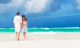 Achtermening van gelukkig romantisch jong paar die bij het strand lopen Royalty-vrije Stock Afbeeldingen