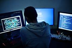 Achtermening van hakker die aan computer werken stock fotografie