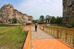 Achtermening van het jonge Aziatische toerist lopen bij gang van de Steenpark van khaongu, Ratchaburi, Thailand stock foto's