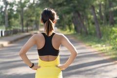 Achtermening van het jonge fitness vrouw lopen op de weg in de ochtend, de Mensen en het sportconcept, Selectieve nadruk stock foto's
