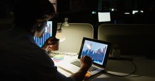 Achtermening van het jonge Kaukasische mannelijke uitvoerende werken aan laptop bij bureau in een modern bureau 4k stock videobeelden