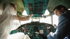 Achtermening van het mooie gelukkige paar van jonggehuwden die in de cockpit zitten stock footage