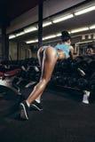 Achtermening van het sexy jonge meisje rusten in de gymnastiek en het leunen op rij van domoren Stock Foto