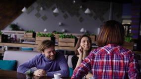 Achtermening van het slanke jonge meisje lopen door de koffie aan haar vrienden Bedrijf van mensen die bij de lijstgroet zitten stock footage