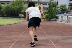 Achtermening van jonge Aziatische sprinter die aanvang op renbaan verlaten bij atletiekstadion royalty-vrije stock afbeelding