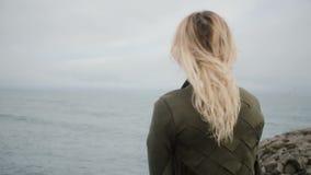 Achtermening van jonge blondevrouw status op kust van overzees en het dromen Het aantrekkelijke wijfje houdt haar en kijkt op wat stock videobeelden
