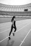 Achtermening van jonge geschiktheidsvrouw die in sportkleding op renbaanstadion sprinten royalty-vrije stock foto