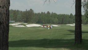 Achtermening van jonge golfspelers die op golfcursus lopen Golf field Groepsmensen die aan het volgende gat op het golfhof lopen stock footage