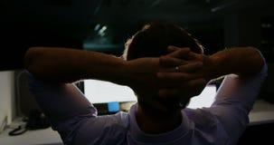 Achtermening van jonge Kaukasische mannelijke stafmedewerker met handen achter hoofdzitting bij bureau in bureau 4k stock videobeelden