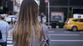 Achtermening van jonge mooie vrouw die de weg in New York, Amerika kruisen Wijfje die op de berijdende auto's en de taxi kijken stock footage