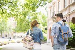 Achtermening van jonge universiteitsvrienden die terwijl het lopen in campus spreken Stock Foto's