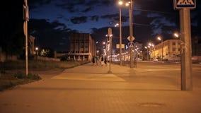 Achtermening van jonge vrienden die op de stad bij avond gaan stock videobeelden