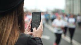 Achtermening van jonge vrouw die smartphone gebruiken aan het filmen van de video van grote groep mensen die de marathon in werki stock videobeelden