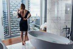 Achtermening van jonge vrouw die witte badjas dragen die zich in badkamers bevinden die uit het venster met badkuip in voorgrond  Royalty-vrije Stock Afbeelding