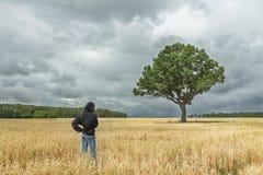Achtermening van jongen zwart sweatshirt dragen met een kap en jeans die het overweldigen van de zomerlandschap bekijken met onwe Stock Afbeelding