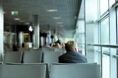 Achtermening van Kaukasische mensenzitting in wachtkamer bij luchthaven, die grijze kostuum en glazen dragen stock afbeeldingen