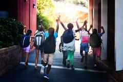 Achtermening van klasgenoten die bij schoolcampus lopen stock foto
