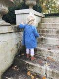 Achtermening van klein blondemeisje die omhoog cementstappen in stedelijke tuin lopen royalty-vrije stock fotografie