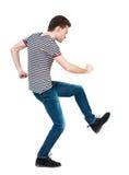 Achtermening van magere kerel grappige strijden die zijn armen en benen golven Stock Foto's
