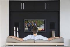 Achtermening van medio-volwassen mens het letten op televisie in woonkamer stock afbeelding