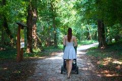 Achtermening van meisje die de kinderwagen in de parkgang, moeder in kleding van achtermening lopen die met de wandelwagen in aar royalty-vrije stock afbeelding