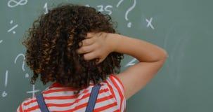 Achtermening van mengen-rasschoolmeisje die haar hoofd in klaslokaal krassen op school 4k stock footage