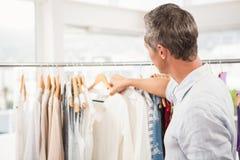Achtermening van mens het doorbladeren kleren stock fotografie