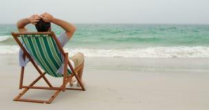 Achtermening van mens het ontspannen met handen achter hoofd op zonlanterfanter bij strand 4k stock videobeelden