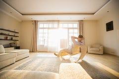 Achtermening van mens het ontspannen op moderne stoel thuis Stock Fotografie