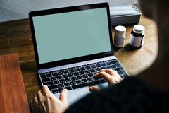 Achtermening van mensen die computerlaptop met behulp van die het lege groene scherm tonen stock afbeelding