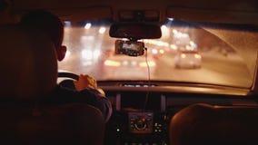Achtermening van mensen drijfauto op weg van stad in avond stock footage