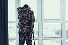 Achtermening van Militair Leaning op Steunpilaar door Venster royalty-vrije stock fotografie