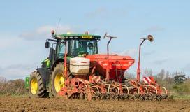 Achtermening van Modern John Deere-tractor boorzaad op gebied Stock Fotografie