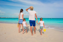 Achtermening van mooie familie met twee jonge geitjes op tropisch strand Stock Foto's