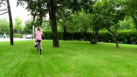 Achtermening van mooie tiener op een fiets in het park stock footage