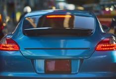 Achtermening van nieuwe sportwagen op de achtergrond van de verkeersstraat stock foto's