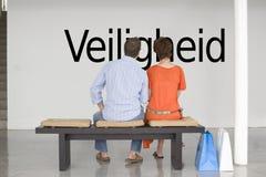 Achtermening van paar die Nederlandse teksten Veiligheid (veiligheid) lezen en het overwegen Royalty-vrije Stock Foto's