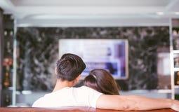 Achtermening van paar het letten op televisie in woonkamer stock foto