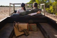Achtermening van paar met wapens rond binnen van wegvoertuig Royalty-vrije Stock Afbeelding