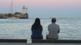 Achtermening van paar volwassen vrienden die oceaan of overzees op stranddijk overwegen stock video