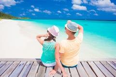 Achtermening van paarzitting op een tropisch strand op de Maldiven Royalty-vrije Stock Foto's