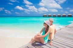 Achtermening van paarzitting op een tropisch strand op de Maldiven royalty-vrije stock afbeeldingen