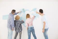 Achtermening van paren die muur in nieuw huis schilderen stock foto's