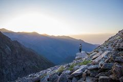 achtermening van persoon die rotsen en mooie bergen bij mistige zonsopgang bekijken, Kyrgyzstan, royalty-vrije stock afbeelding