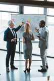 achtermening van professionele multi-etnische collega's die bedrijfsgrafieken en grafieken bespreken royalty-vrije stock afbeelding