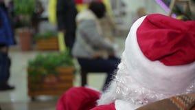 Achtermening van Santa Claus die bezige voorbijgangers in overvol handelscentrum bekijken stock video