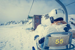 Achtermening van skiër die een lift berijden Royalty-vrije Stock Fotografie